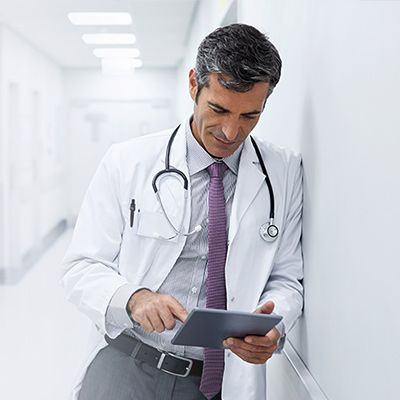 Physician leaning against a wall looking at a tablet.