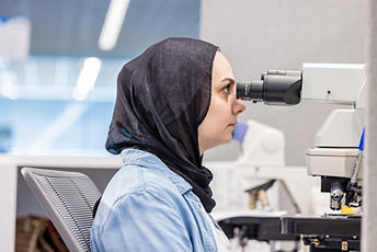 Lab worker using a microscope for pathology purposes