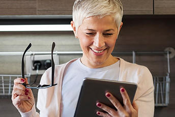 Woman taking off glasses to look at device