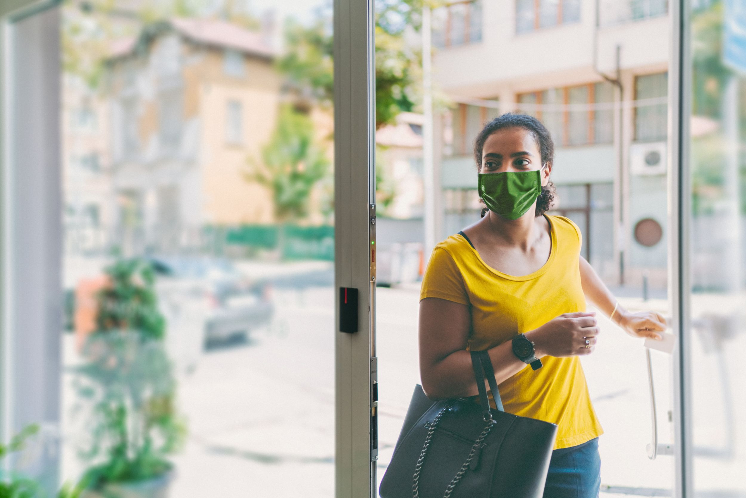 Woman with mask walking into a Quest patient service center.